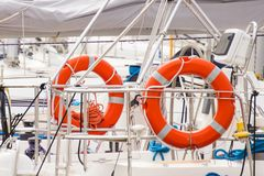 Parts of yacht, Orange lifebuoy on sailboat, safety travel concept. Parts and detail of yachting, Orange lifebuoy on deck of sailboat, concept of safety travel Stock Photo