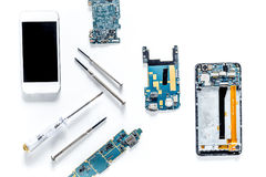 Parts of disassembled cell phone and screwdrivers on white background top view stock image