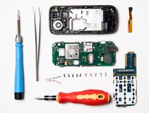 Parts of the disassembled mobile phone, screwdriver, plastic case, broken screen and parts lay out flat lay. Service center for mobile phone repair, overhead royalty free stock images