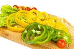 Parts fraîches de poivre avec des tomates-cerises Photographie stock libre de droits