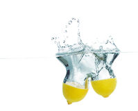 Parts of lemon dropped in water with splash. Lemon in water with splash on white background Stock Image