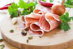 Parts minces de jambon avec des herbes et des épices photographie stock
