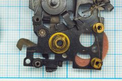 Parts old retro film SLR camera on graph paper. Parts are completely disassembled old retro film SLR camera on graph paper, close-up Royalty Free Stock Images