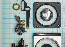 Parts old retro film SLR camera on graph paper. Parts are completely disassembled old retro film SLR camera on graph paper, close-up Stock Photos
