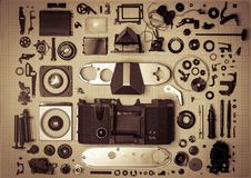 Parts old retro film SLR camera on graph paper. Parts are completely disassembled old retro film SLR camera on graph paper, close-up, toned Royalty Free Stock Images