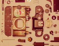 Parts old retro film SLR camera on graph paper. Parts are completely disassembled old retro film SLR camera on graph paper, close-up, toned Royalty Free Stock Photos