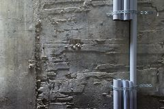 Parts of plastic pvc pipes fixed on the wall. Parts of plastic pvc pipes fixed to a non-uniform concrete wall Stock Images