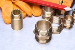 Parts of plumbing fitting with wrench and tools Royalty Free Stock Photos
