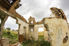 Parts of a ruined house with dramatic sky - different textures and herbs Royalty Free Stock Image