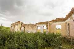 Parts of a ruined house with dramatic sky - different textures and herbs Royalty Free Stock Images