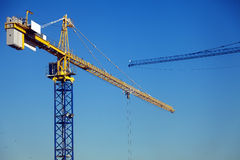 Tower Cranes. Parts of two tower cranes on a clear day Royalty Free Stock Images