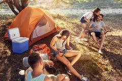 Party, располагаться лагерем людей и группа женщин на лесе они ослабляя, поя песню Стоковое Изображение