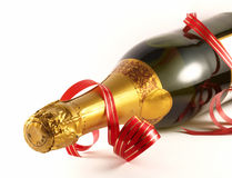 Party!. An unopened champagne bottle with a red ribbon isolated on white Royalty Free Stock Photo