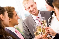 At party. Photo of happy man holding flute with champagne and smiling at colleagues during party Stock Images
