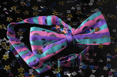 After the Party. A brightly colored bow tie sits on a black surface.  There is confetti strewn around the tie Royalty Free Stock Photo