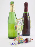 Party. Photo of two bottles of champagne and a glass of champagne with confetti streams around it Stock Images
