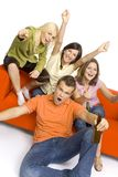 Party on!. Three young woman and a man are sitting on (and next to) the orange couch. Two of them are holding beer. They're shouting and gesturing Royalty Free Stock Photo