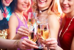 Party. Beautiful girls clink glasses of champagne at a party Royalty Free Stock Photo
