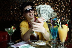 Party. The young guy sits in night club with a lot of money in a hand and a big smile Royalty Free Stock Photo