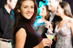 Party. Young friendly woman looking at camera while a party