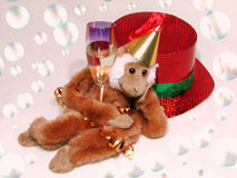 After party. The monkey with glass is lying near red hat Royalty Free Stock Photo