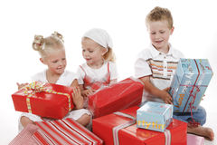 Party. Three cute children celebrating special occasion with several gifts Royalty Free Stock Photography
