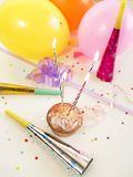 Party. Four burning candles at cupcake; balloons, confetti and noise makers at background stock image