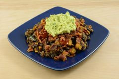 Party appetizer on blue plate. Party appetizer made from sweet potatoes, black beans, bacon and guacamole on blue plate Royalty Free Stock Photography