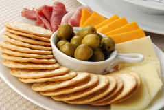Party Appetizers. A plate of crackers with pimiento stuffed manzanilla olives, meats and cheeses Royalty Free Stock Images
