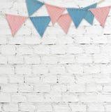 Party as bandeiras que penduram no fundo branco da parede de tijolo Fotografia de Stock Royalty Free