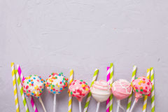 Party background. Colorful cake pops and paper straws on  grey Stock Image