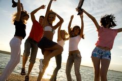 Party on beach. Group of happy young people dancing at the beach on  beautiful summer sunset Royalty Free Stock Images
