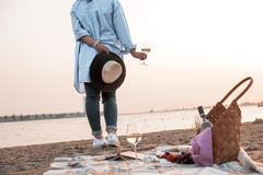 A party on the beach at sunset and a girl with a glass of wine. Romantic evening in the summer by the sea. Picnic. Copy space.  royalty free stock images