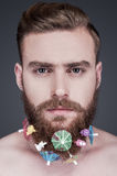 Party beard. Portrait of handsome young shirtless man with toys and cocktail parasols in his beard looking at camera while standing against grey background Royalty Free Stock Image