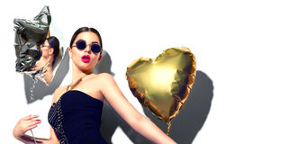Party. Beautiful fashion model girl with colorful heart and star shaped balloons Royalty Free Stock Photo