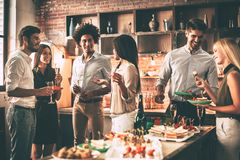 Party with best friends. Group of cheerful young people enjoying home party with snacks and drinks while communicating on the kitchen royalty free stock photos