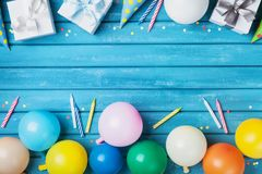 Party birthday banner or background with balloons, gift, carnival cap, confetti and candle. Copy space for greeting text. Party birthday banner or background Royalty Free Stock Photography