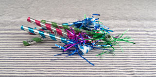 Party blower noisemakers on a striped tablecloth Stock Photos