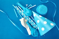 Party blue paper hat. Celebration Flat lay. Party blue hat polka dot background. Birthday paper hat, candles, tubes and balloons stock photography