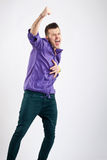 Party boy screaming. With hand in the air on studio background Stock Photo