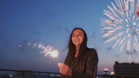 Party or bright nightlife at firework time. Young brunette charming girl dancing and waving hands with sparkle lights stock footage