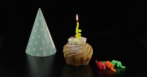 Party. Cake and festive candle on it. Celebrate birthday. Party. Cake and a yellow festive candle on it. Colored party hat. Black background. Celebrate an event stock photos
