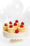 Party Cakes. Strawberry party cupcakes on pretty cake stand with balloons in background Stock Photos