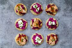 Blinis with creamy beetroot, goat cheese and hot smoked salmon. Party canapes of blinis with creamy beetroot, goat cheese and hot smoked salmon Royalty Free Stock Photos