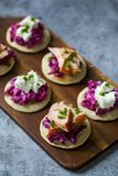 Blinis with creamy beetroot, goat cheese and hot smoked salmon. Party canapes of blinis with creamy beetroot, goat cheese and hot smoked salmon Royalty Free Stock Images