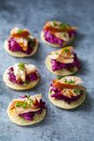 Blinis with creamy beetroot and hot smoked salmon. Party canapes of blinis with creamy beetroot, hot smoked salmon and chives Royalty Free Stock Image