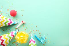 Party caps, blowers and confetti. Birthday party caps, blowers and confetti on mint background stock images