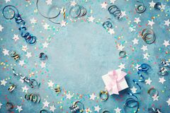 Party, carnival or birthday frame with colorful confetti, gift box and streamer on vintage blue table. Christmas greeting.