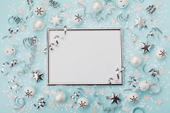 Party carnival christmas background decorated silver frame with confetti, balls and star on turquoise desk top view. Flat lay. Holiday mockup invitation Stock Image