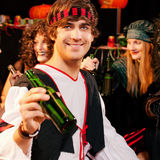 Party for carnival or Halloween. Group of young people celebrating a carnival or Halloween party in costumes drinking beer Royalty Free Stock Photography